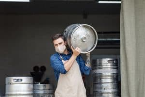 Young man working at warehouse in brewery or employee with keg. Handsome millennial man with tattoos in protective mask and apron carries metal barrel and looks at camera, free space