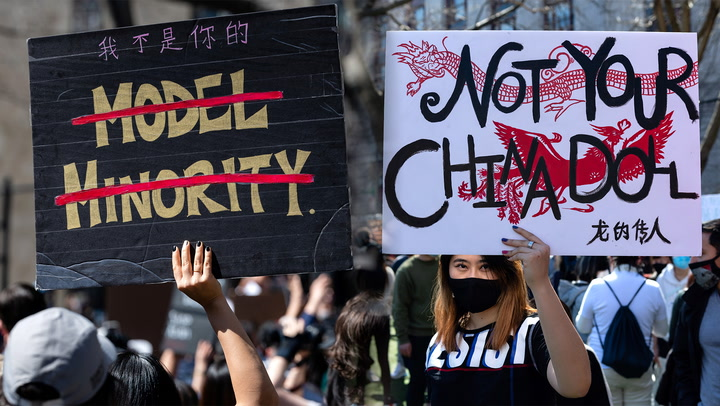 "Signs saying ""Not Your China Doll"" and ""Model Minority"" with lines through it."